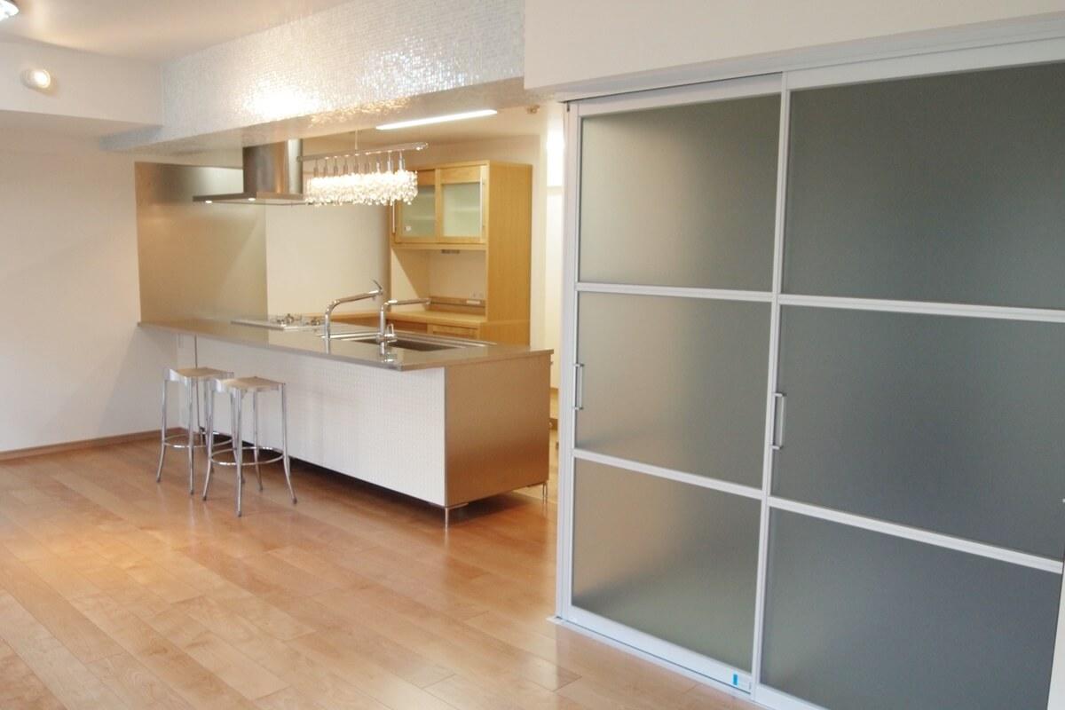 キッチンの隣はアルミフレームの扉で仕切られた和室