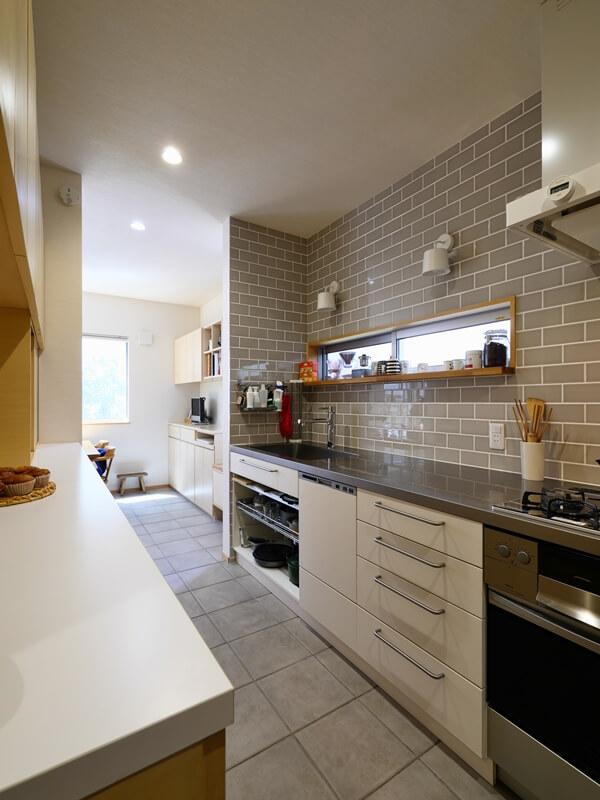 グレーのタイルの壁と、窓にカウンターのあるキッチン