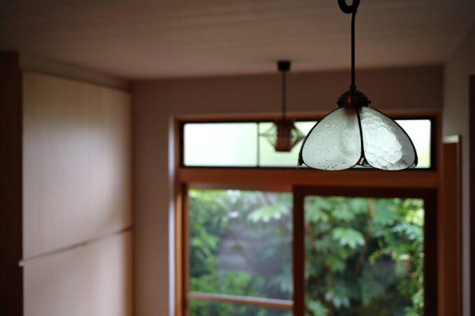 照明は古い家で使っていた扉のガラスで製作。庭に出る木製建具は再利用し、雨戸を新設しました。