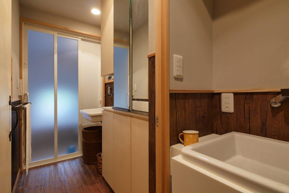 洗面台の隣に鏡扉のある壁面収納