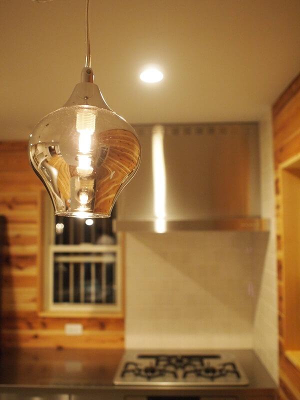 キッチンの透明感あるペンダントライトとステンレスレンジフード