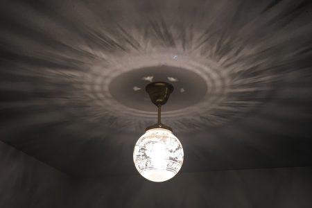 玄関ホールの照明の陰影が漆喰の天井に映り込む